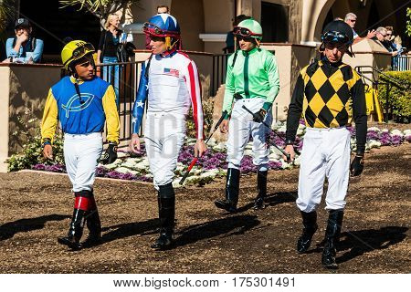 DEL MAR, CALIFORNIA - NOVEMBER 25, 2016:  Group of four jockeys entering the paddock area at the Del Mar racetrack.