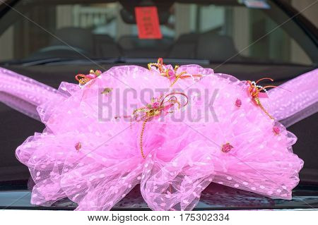 Wedding car in the front of house. Luxurly car decoration as a wedding car with pink ribon.