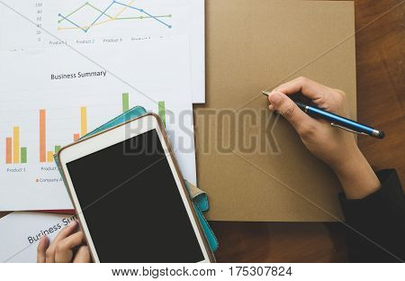 Top - View Of  Hand Holding Pen With Business Summary Or Business Plan Report With Charts And Graphs