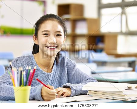 happy asian elementary school student studying in classroom looking at camera smiling