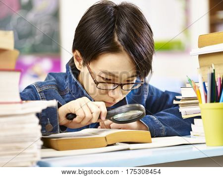 asian pupil with glasses using a magnifier to enlarge the words in a thick book.
