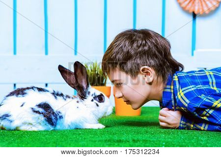 Happy child boy lying on a grass with Easter Bunny in spring garden decoration. Kid's fashion. Easter holidays.
