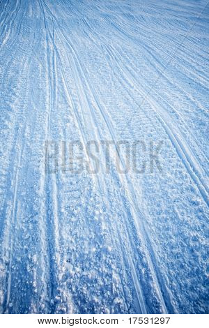 A snow texture of snowmobile tracks converging into the distance