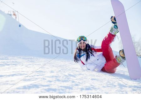 Sportwoman in glasses with snowboard on mountain in winter