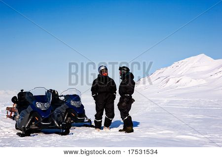 A group on a winter snowmobile adventure over a barren winter landscape