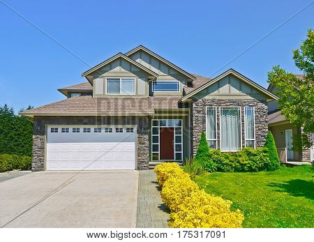Luxury family house with concrete driveway to the garage on blue sky background