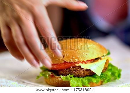 Hamburger fast food with ham on wooden board . Group of hamburger on blurred background. Piece of cheese hanging from sandwich. Close up of female hand reaches for cheeseburger is not in field.