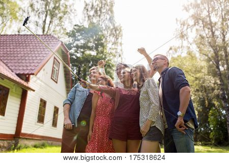 leisure, party, technology, people and holidays concept - happy friends taking picture with smartphone selfie stick at summer garden