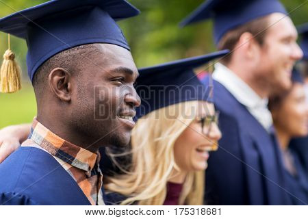 education, graduation and people concept - group of happy international students in mortar boards and bachelor gowns outdoors