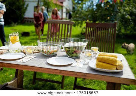 holidays, eating, mealtime and food concept - people coming to served table with dinner at summer garden party