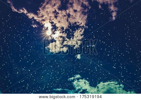 Amazing blue dark night sky with many stars bright full moon and cloudy. Outdoor at nighttime with moonlight. Pretty nature use as background. Cross process and vintage effect tone.