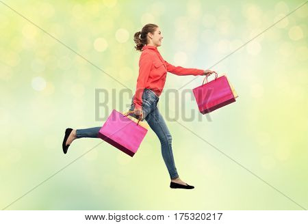 sale, motion and people concept - smiling young woman with shopping bags running in air over summer green lights background