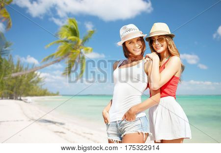summer holidays, vacation, travel and people concept - smiling young women in hats and casual clothes over exotic tropical beach with palm trees background