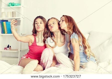 friendship, people, pajama party and technology concept - happy friends or teenage girls with smartphone taking selfie at home