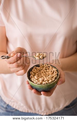 Closeup of woman's hands holding bowl with organic whole wheat cereal. Healthy Breakfast or snack. Healthy food and eating.