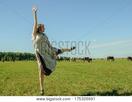Beautiful woman in traditional dress dances meadow at horses background
