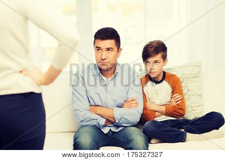 people, misbehavior, family and relations concept - upset feeling guilty or displeased father, son and angry mother at home