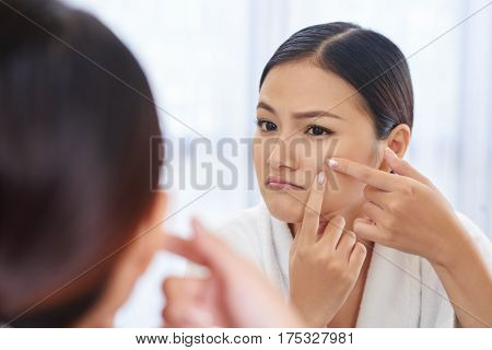 Unhappy beautiful Asian woman popping pimple on her cheek