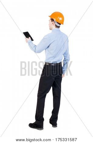 Backview of business man in construction helmet stands and enjoys tablet or using a mobile phone. Standing young guy. Rear view people collection.  backside view of person.