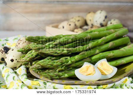 Spring season dish - fresh green asparagus and quail eggs on wooden table