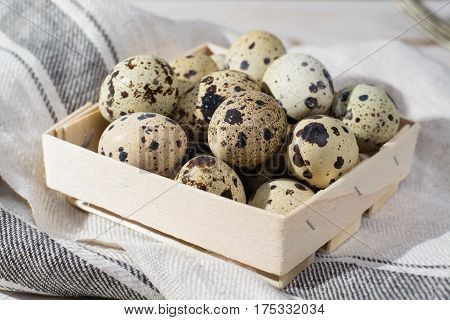 Small quail eggs in wooden box Easter concept diet meal