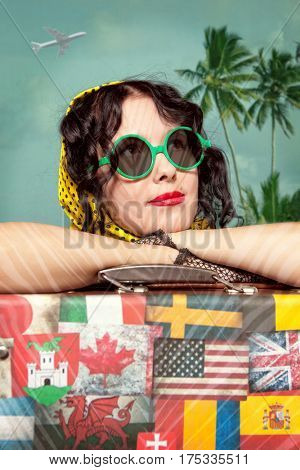 Woman traveler embraces a vintage suitcase. Suitcase with stamps flags representing each country traveled. Photo in old image style