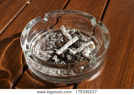 Glass ashtray with cigarette butts and ashes on wooden board