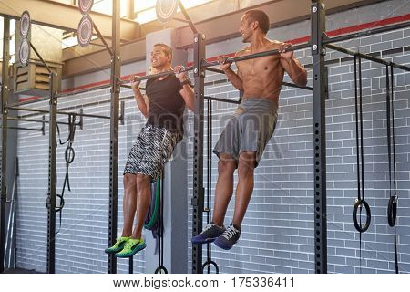 Gym partners buddies doing pull ups in a industrial looking gym, muscular fit lean men exercising