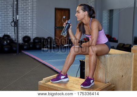 Fit lean woman taking a break rest, hydrating drinking water from bottle in gym