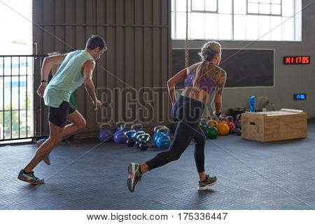 Man and woman race each other to complete laps of sprint sessions in gym during exercise fitness class session
