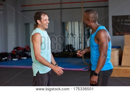 Happy smiling gym buddies multi ethnic racial friends talking having fun in gym