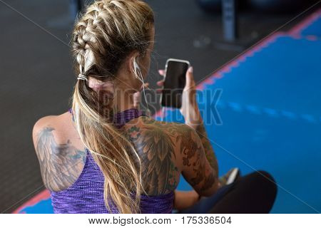 Anonymous woman in sportswear sporty attire with tattoos using smartphone in gym, fitness exercise app music concept