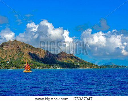 sailboat passing by diamondhead near waikiki beach