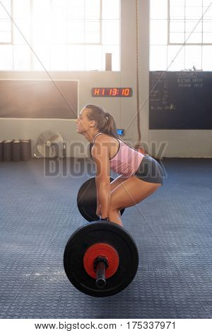 woman with power and good technique lifting weights deadlift in gym