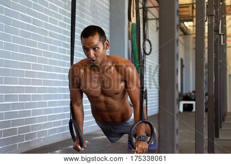 Determined man working out in gym with gymnastic rings for strength and crossfit core exercise