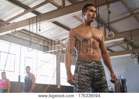 Fit muscular shirtless man takes a break while lifting weights in gym