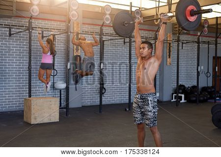 Ripped fit man in gym lifting heavy bar while others workout in the background