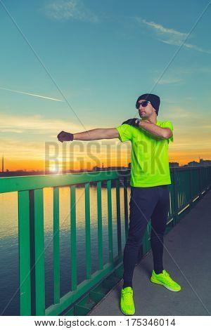 Urban jogger stretching on the bridge at sunset / sunrise.