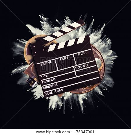 Retro film production accessories with powder explosion on background. Concept of film-making.
