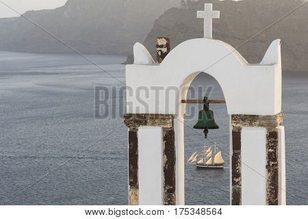 Traditional church belfry and sailing boat at sunset in Oia Santorini Greece