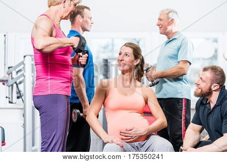 Pregnant woman with senior people working out at the gym with personal trainer