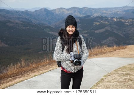 Hiker portrait. Female hiking woman happy and smiling with her camera during hike trek on Omuro volcano.