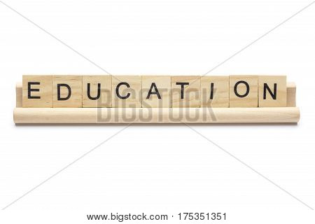 Word ''education'' on scrabble wooden letters on a rack isolated on white background.