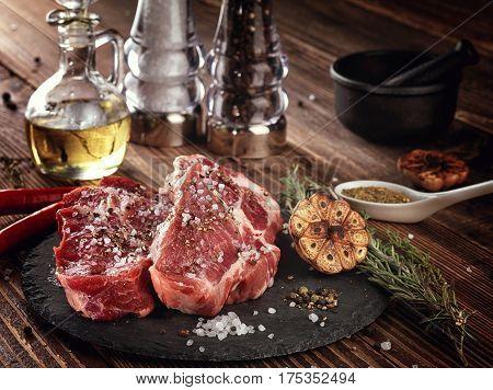 Raw Pork Neck Steak On A Stone Plate.