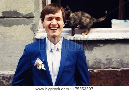 Little Cat Cathes Fiance's Ear While He Stands Behind An Open Window