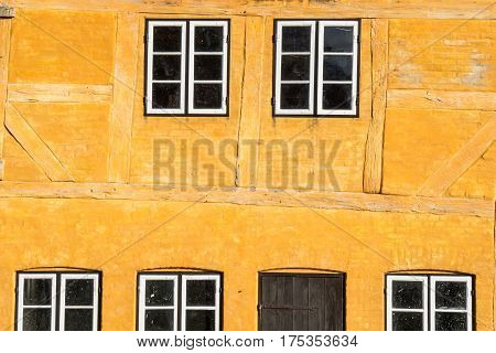European building styles. detail of yellow timber framed house with white small windows