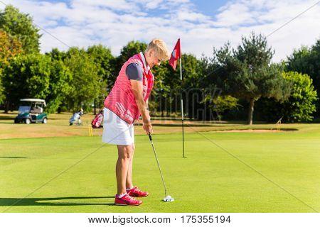 Senior golf playing woman putting on green