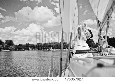 Wedding Couple In Love At Small Sailboat Yacht On Lake. Black And White Photo.