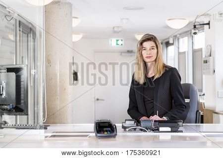 Sales woman, dressed in classy black, sitting behind the counter of a ticket booth in an office