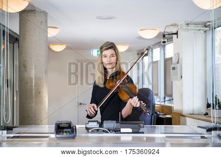 Classical Musician, playing a violin, sitting behind a counter at a ticket booth, selling tickets